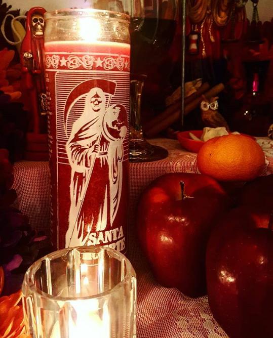 Santa Muerte rote Votovkerze und rote Figur auf einem Altar
