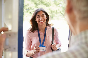 Senior man opening front door to young woman showing ID card.jpg