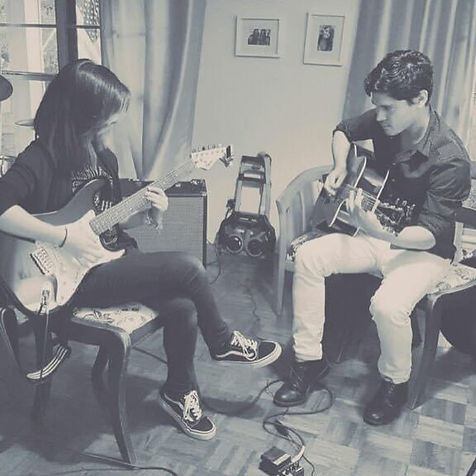 Benji Lamar teaching guitar to a teenager