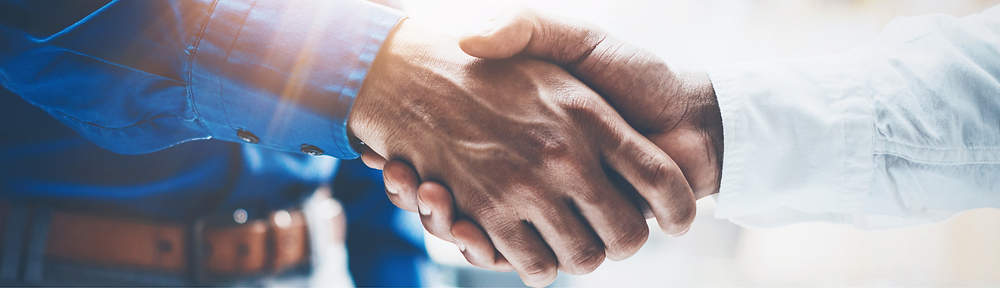 This image shows two men shaking hands possibly showing an agreement on a deal, sale, etc.