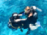 Two divers in black scuba diving suits,