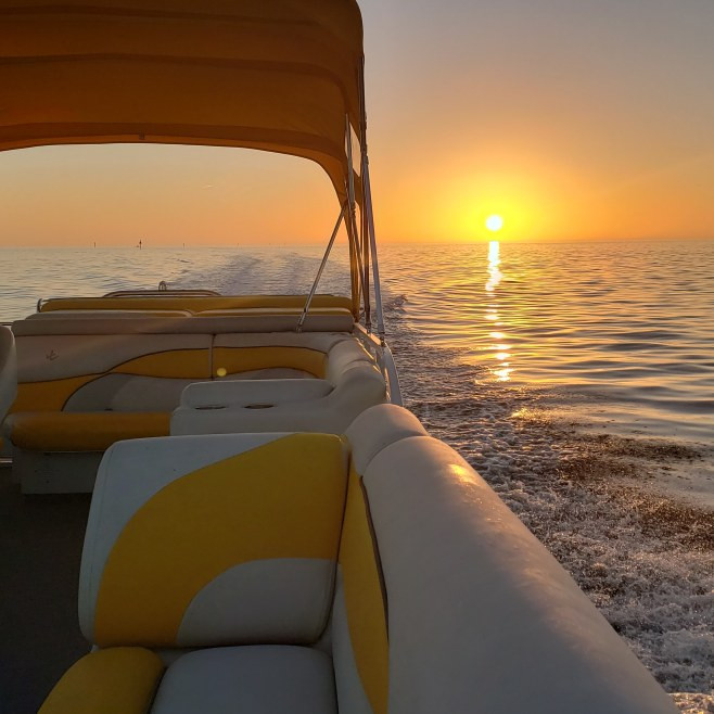 section of boat seat with sunset on water