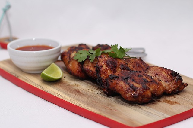barbecue chicken with bowl of sauce, lime on a cutting board