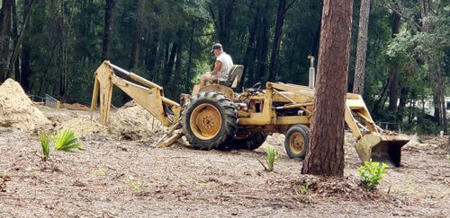 Rob on tractor with backhoe to dig trenches on campground.