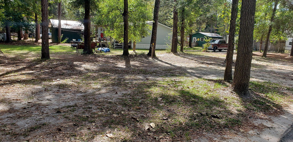 trees, buildings, sand, grass for small camper or tent in RV campground