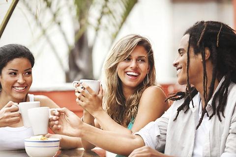 Three diverse adults enjoying conversation over coffee