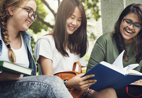 Three diverse, female high school students enjoying a book together