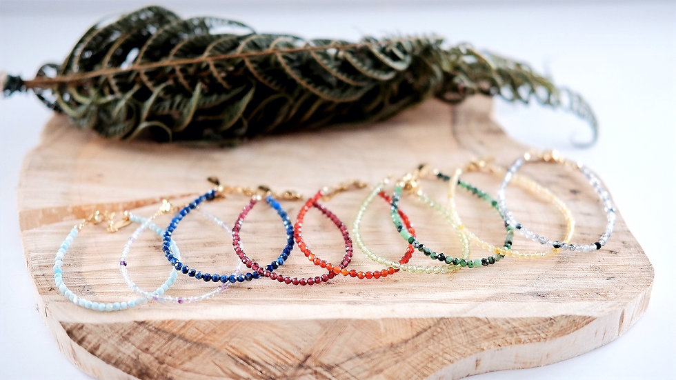 Dainty 3mm faceted natural gemstone bracelets presentation on a piece of wood and a fern branch