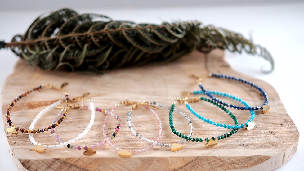 A large shot on several of dainty 3mm faceted natural gemstone with a gold surgical steel presented on a piece of wood