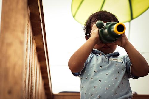 Child looking through handheld toy telescope