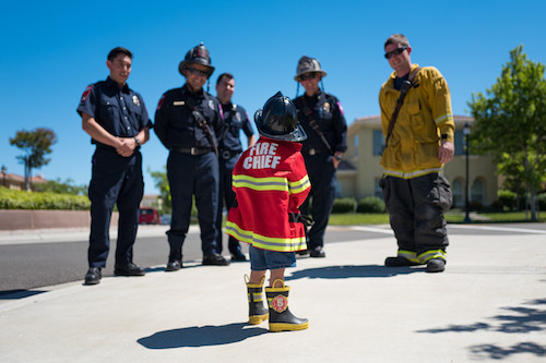 Child in fireman costume meeting real firefighters