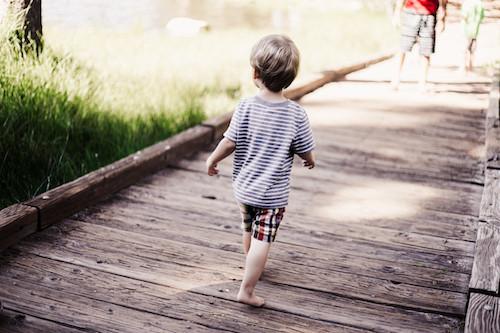 Child walking on lake pier