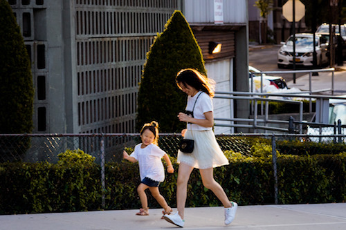 Mother and daughter running down sidewalk