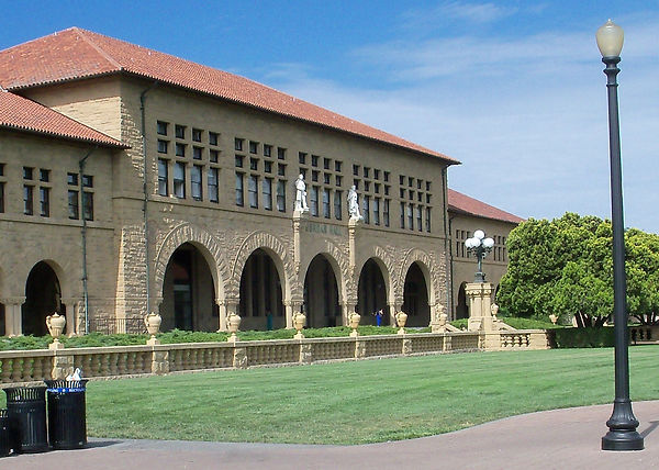 An image of Jordan Hall. Like most of Stanford's building in the Main Quad, it is sandstone with a red tile roof. It has arches in a manner resembling the Spansh missions. Green letters spell out: Jordan Hall.