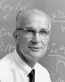 A black and white photo of William Shockley. He is balding, wearing a shirt in tie, as he poses in front of a blackboard covered in mathematical equations.
