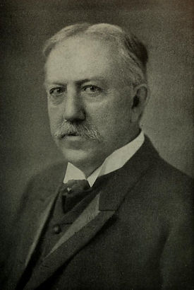 A photo portrait of David Starr Jordan. He is an older white man wearing a suit and tie. He has a mustache.