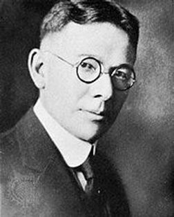 A black and whte photo of Lewis Terman. He has short black hair and is wearing round glasses and a suit.