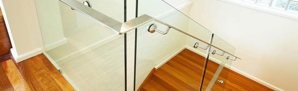 Glass staircase with stainless steel handrail and radius corners
