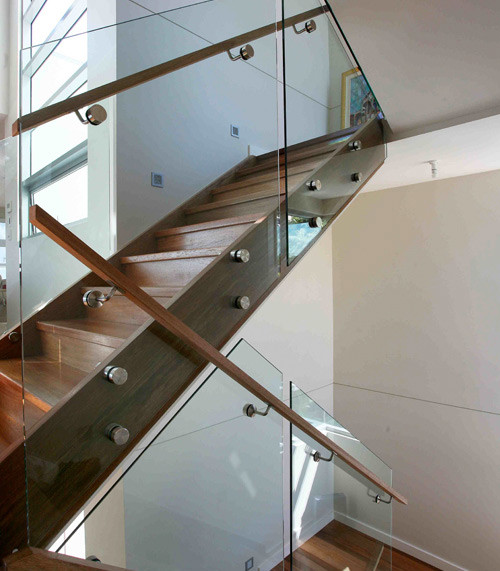 Multi level Framless staircase with wooden handrail to complment the floor