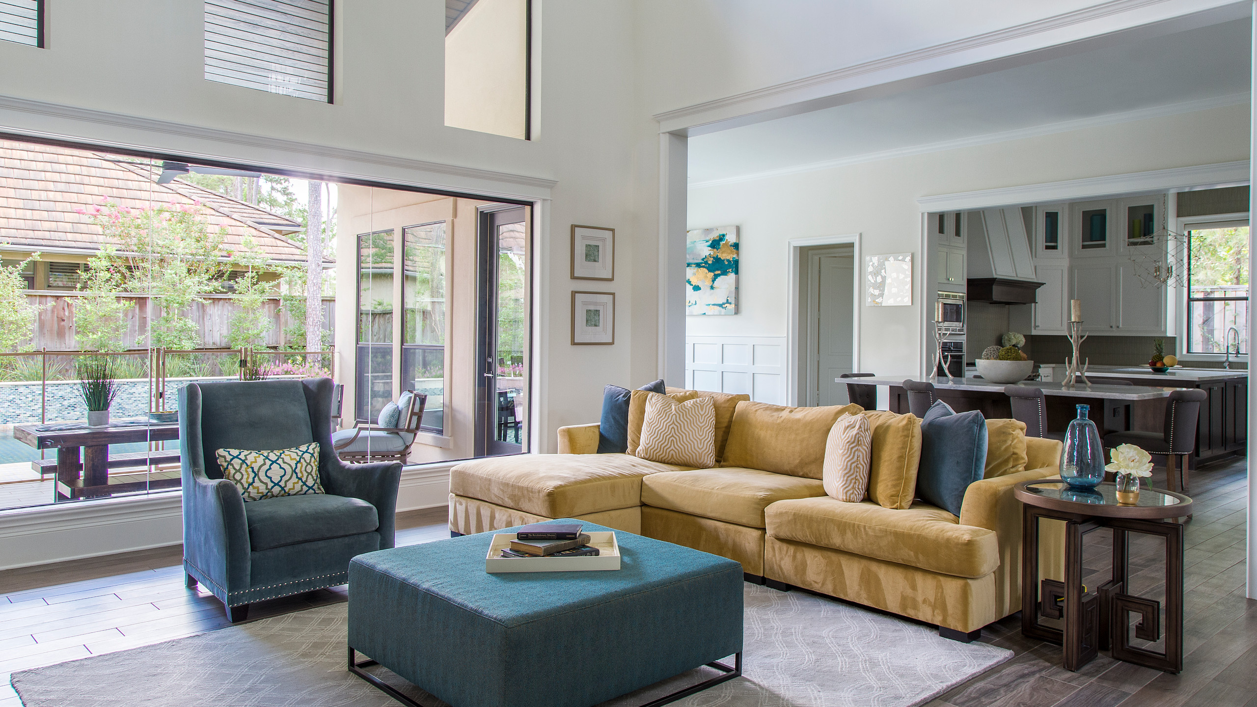 transitional living room of an open concept home. accents of bright colors pop against crisp white walls
