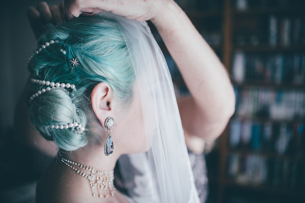 Bride puts on her wedding veil, Seattle wedding planner, Seventh and Central, explains common wedding traditions.