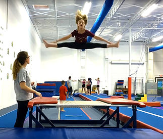 Girl Straddle Jump on Double Mini Trampoline with coach