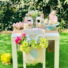 Easter table with cupcakes, bunnies and flowers