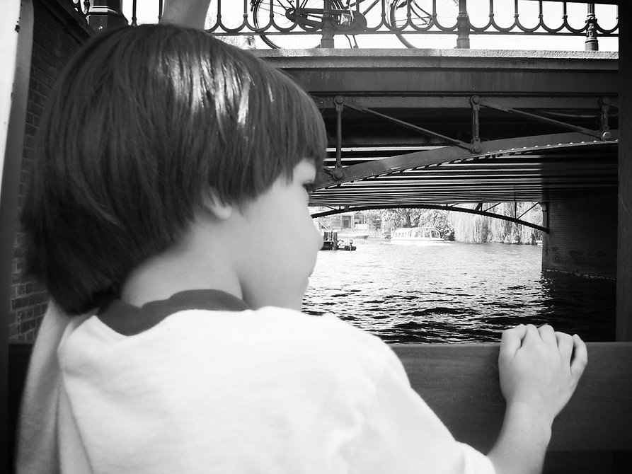 Young child glancing under a bridge, off into the distance.