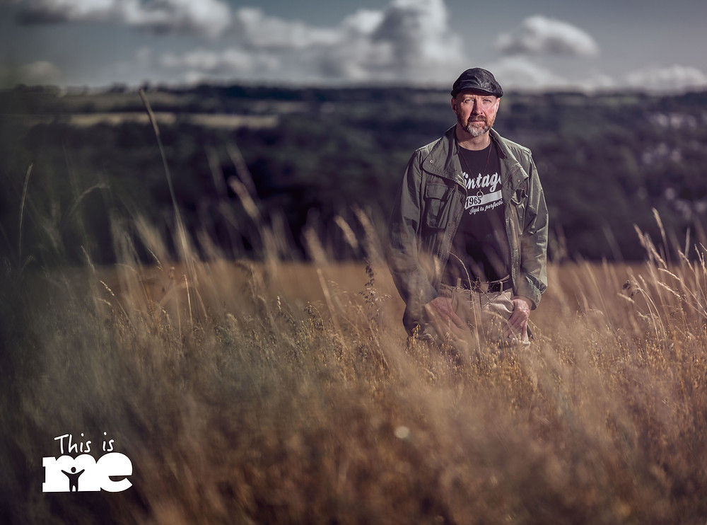 photographer Phil Benton standing in a grassy field looking determined and happy