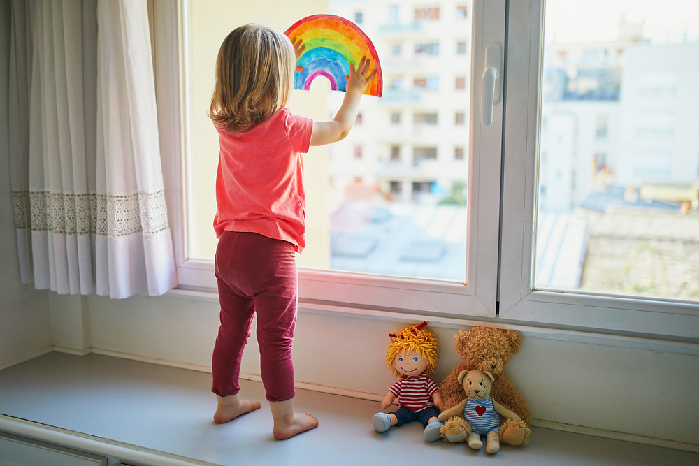 Toddler sticking a rainbow on her bedroom window, sign of hope during lockdown 2020.