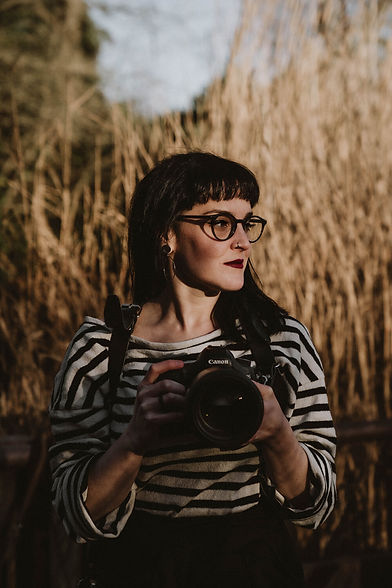 Woman holding a camera in a nature setting.