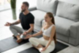 calm-millennial-couple-meditating-lotus-