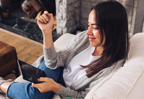 modern-woman-sitting-sofa-using-tablet_2