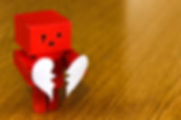Red paper robot holding a broken heart