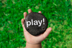 Baby Holding Up A Black Pebble With The