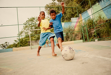 Two boys playing football barefoot
