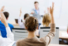 Young woman raising hand in classroom