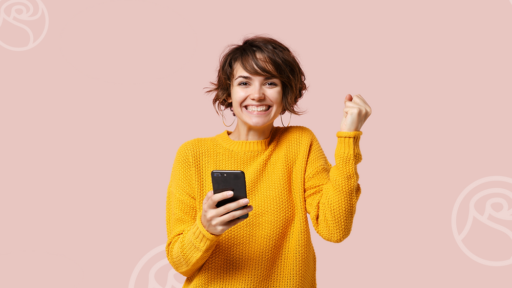 """Woman holding a phone representing digital health is excited. She's making a gesture that says """"winning""""!"""
