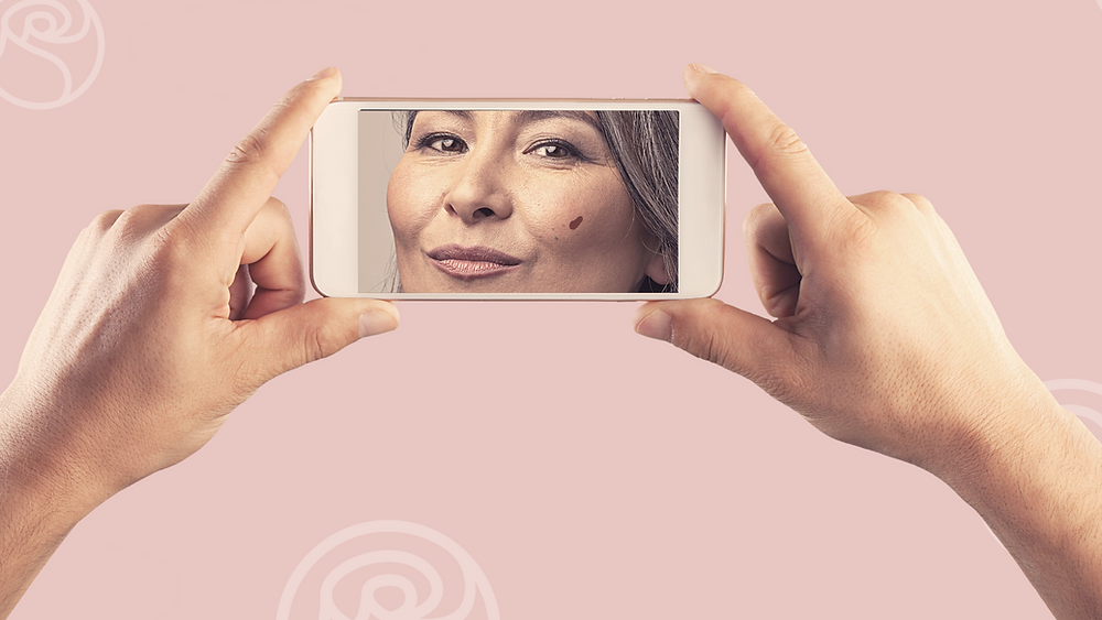 Woman examining a spot on her face on her smartphone..