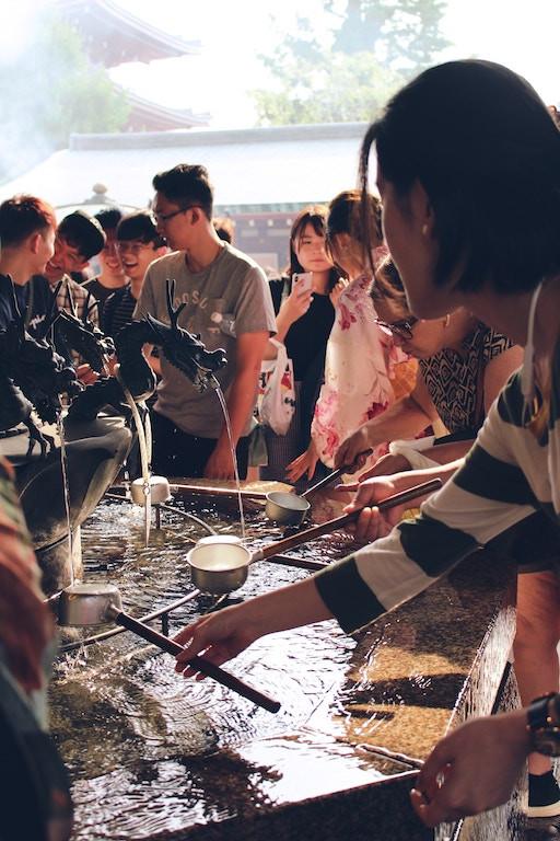 Visiteurs qui se lavent les mains à la fontaine du temple Senso-Ji, à Asakusa, à Tokyo