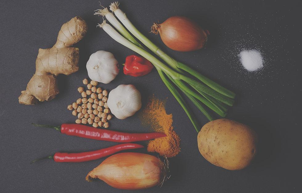 Close up of Raw ingredients like green onionsm garlic, chickpeas, chili peppers, onion, potato's