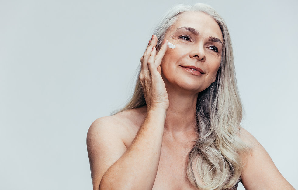 Senior woman putting on anti aging cream on her face and looking away. Female applying moi