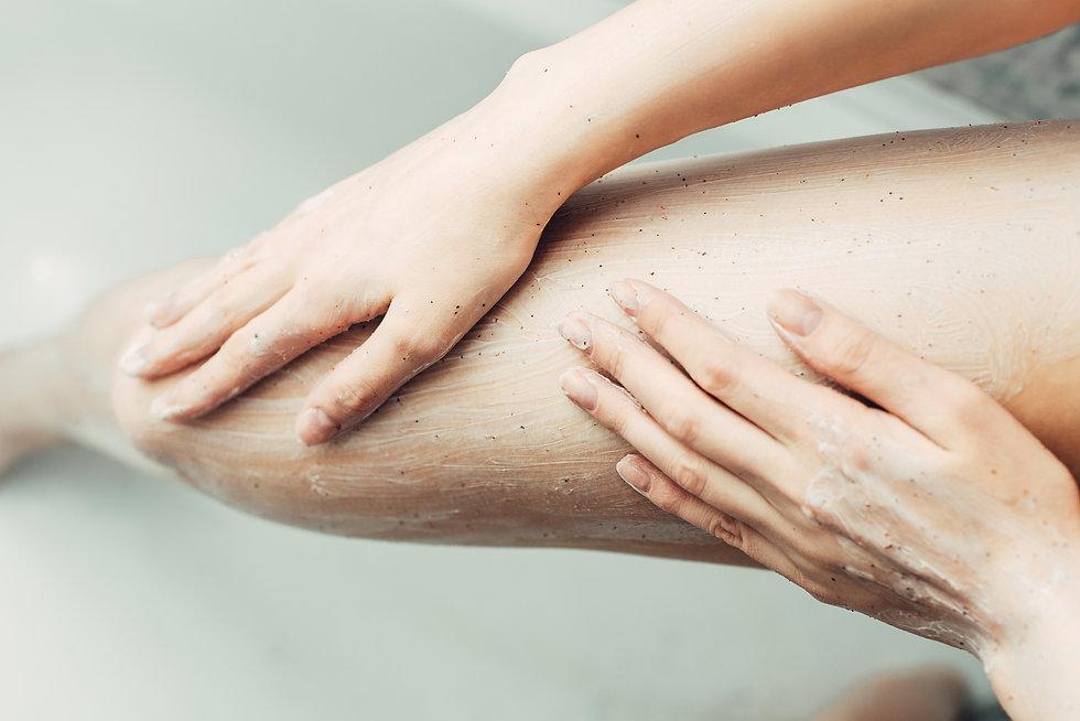 girl applies scrub to foot.jpg