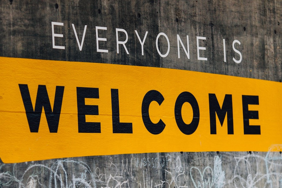 Everyone is Welcome painted on concrete wall.