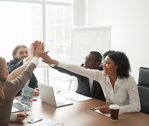 Excited african and caucasian business team giving high five at office meeting motivated by victory,