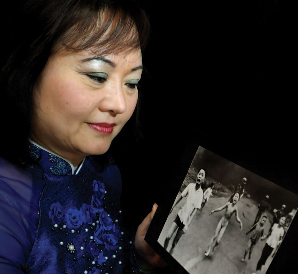 Kim Phuc looks at the famous photo of herself as a child