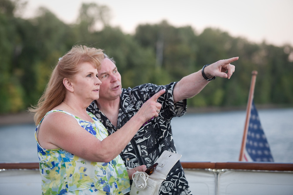 older couple on boat pointing into distance