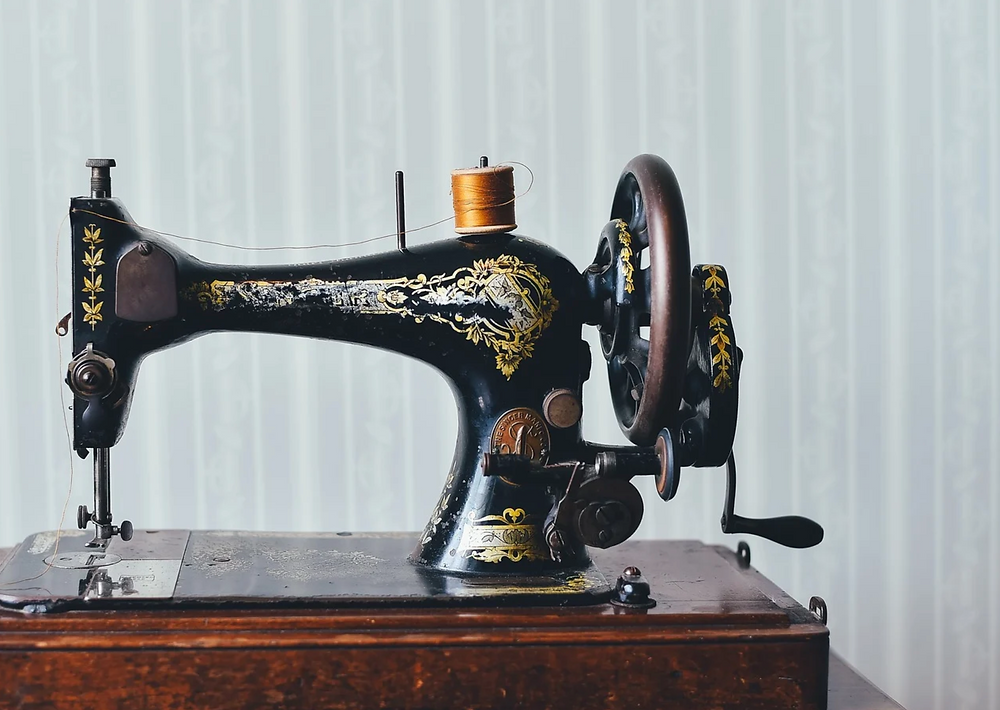 an old sewing machine with yellow thread