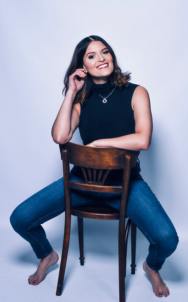 Joyce Espino sitting on a chair, smiling, and posing.