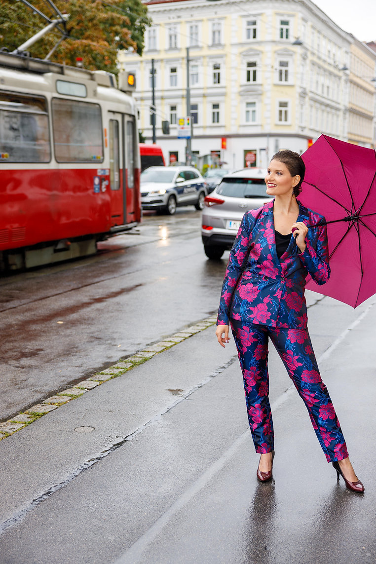 Joyce holding an umbrella in the streets of Vienna, with a blue and pink suit and a big smile, looking to the side.